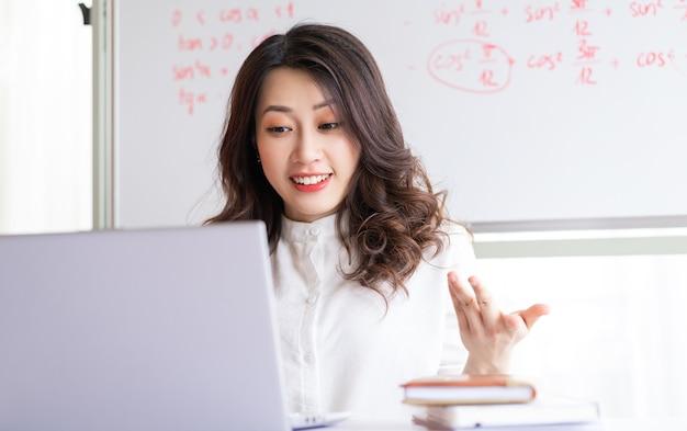 집에서 온라인으로 가르치는 아시아 여성 교사