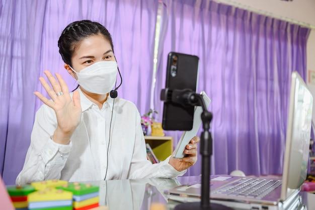マスクをかぶったアジアの女性教師は、教育用のオンラインビデオ会議システムを使用して、コンピューター画面を介してオンラインで勉強するように生徒に教えています。