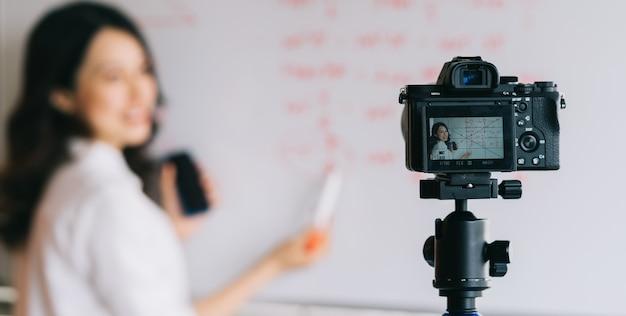 アジアの女性教師がオンライン教育の授業を録音しています