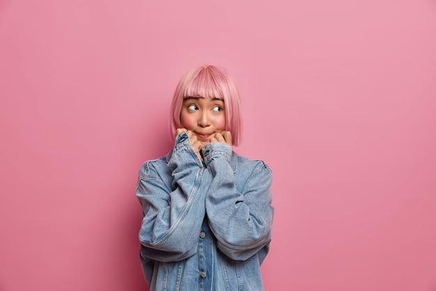 분홍색 머리카락을 가진 아시아 여성 십대, 턱 아래에 손을 유지하고 특대 데님 재킷을 입은 사려 깊은 표정으로 외모, 무언가를 기억하려고 시도하고 문제 해결 방법을 상상합니다.