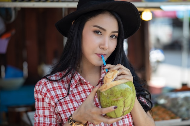 Asian female tourist are drinking coconut water at amphawa water market