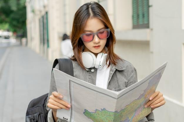 아시아 여성 관광객이 길을 찾기 위해 지도를 읽고 있다