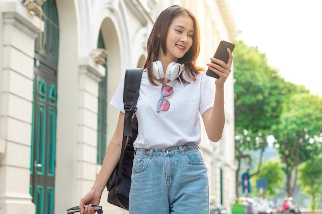 아시아 여성 관광객이 길을 찾기 위해 휴대전화를 사용하고 있습니다.