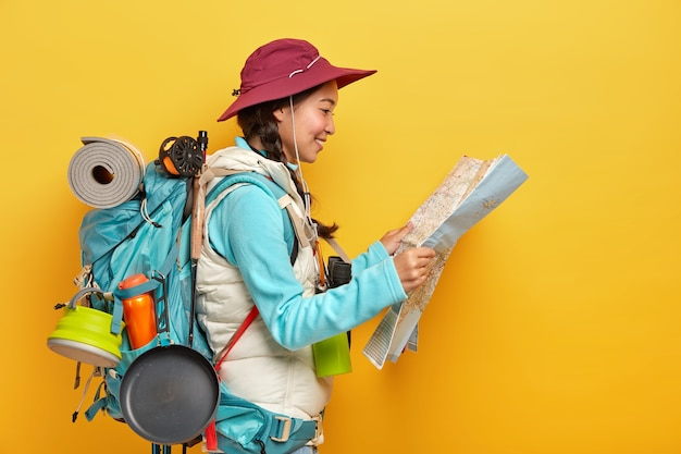 Asian female tourist studies map, finds new destination to explore, travels alone, wears cap and active wear, carries big rucksack