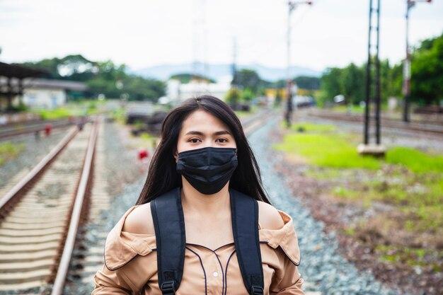 マスクを身に着けているアジアの女性観光客はcovid-19を防ぎます