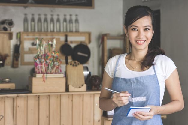 Азиатский официант женского пола в заказе написания передника