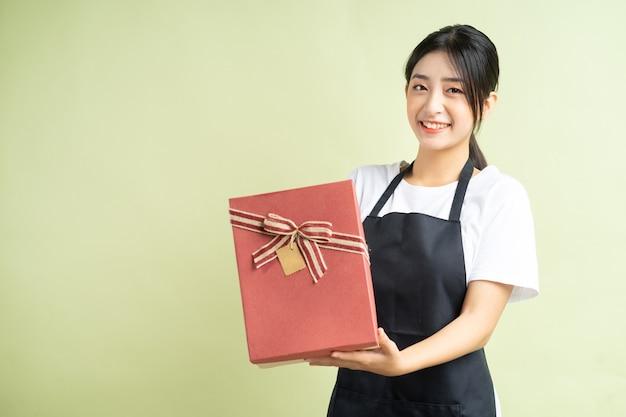 ギフトボックスを保持しているアジアの女性ウェイトレス