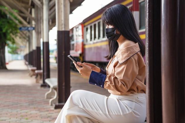 Азиатская женщина в маске с помощью мобильного телефона