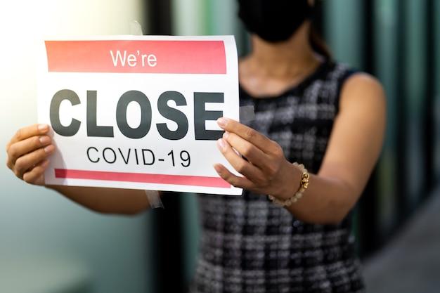 의료 마스크를 착용 한 아시아 여성은 사무실 문과 창문에 covid-19 유행성 사인 배너로 인해 임시 폐쇄 됨