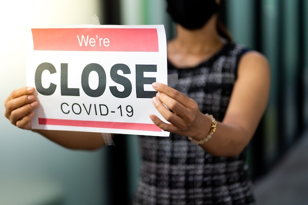 Asian female wearing medical mask puts a temporary closed due covid-19 pandemic sign banner on door and windows at office