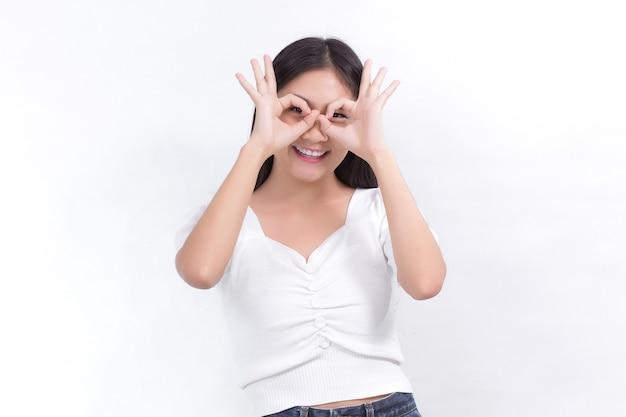 長い黒髪のアジアの女性は白いシャツを着て、白い背景に手のオーケーサインを示しています