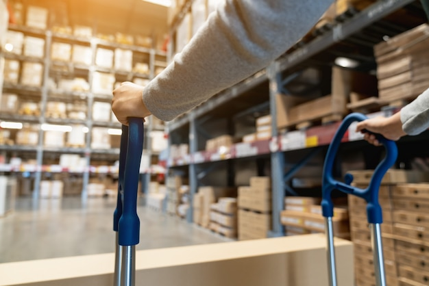 Asian female worker pulling pallet truck in storage warehouse with background