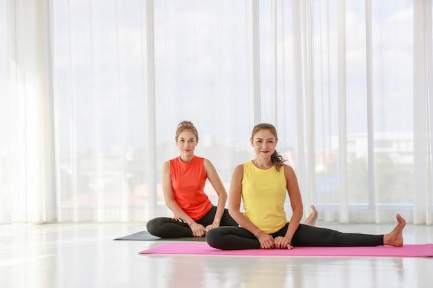 アジアの女性ヨガ講師が、クラスで基本的なヨガのレッスンを実践するために、新入生を指導し、トレーニングしています。