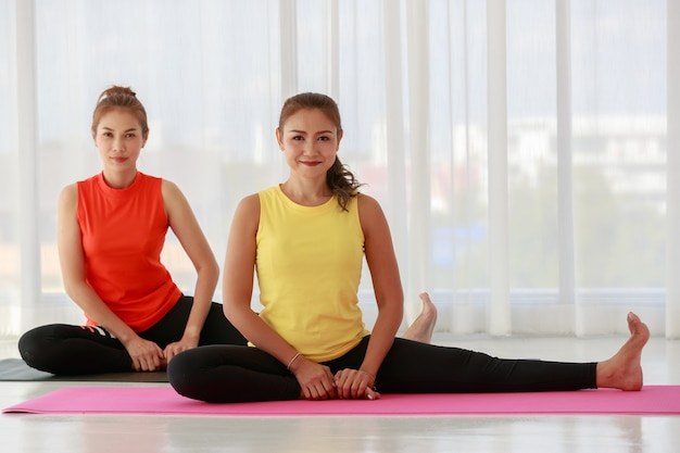 Asian female yoga teacher leading and training new comer student to pratice the lession of basic yoga during class.