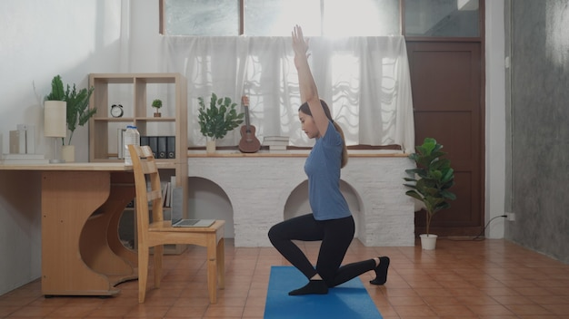 아파트에서 훈련 및 운동 요가 포즈를 위해 컴퓨터 시계 온라인 수업을 사용하는 아시아 여성