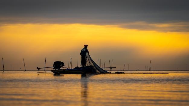 朝の湖で魚を捕まえるための木製ボートに乗ってアジアの漁師