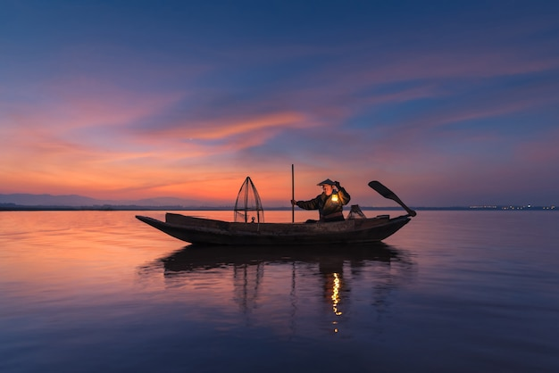 Asian fisherman with his wooden boat in nature river at the early morning before sunrise