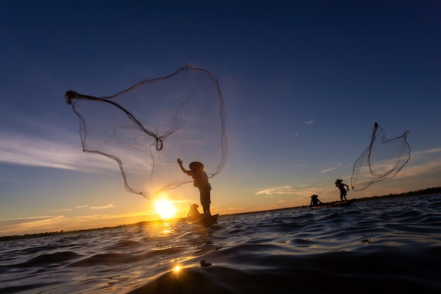 Asian fisherman on wooden boat casting a net for catching freshwater fish in nature river.