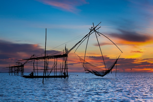 Asian fisherman on wooden boat  with sunrise