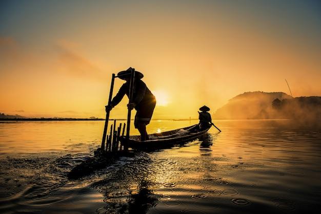 Asian fishermen on boat fishing at lake, thailand countryside
