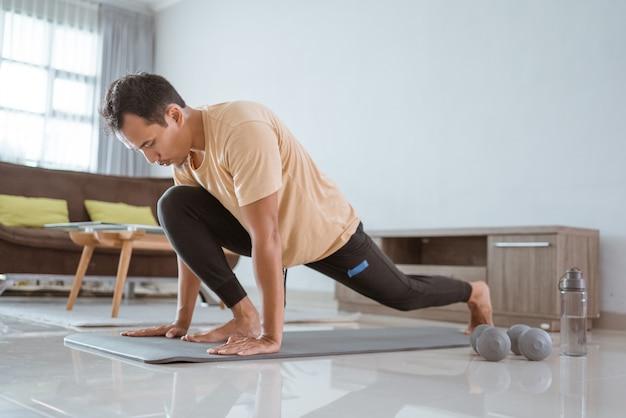片足を持ち上げて右を見ながら、アジアンフィットの若い男性のエクササイズマット。