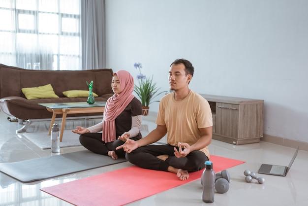 アジアのフィットネスカップル、男性と女性が自宅で一緒に運動して居間でヨガをしている