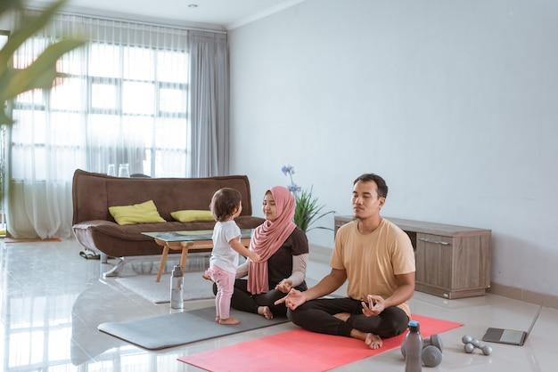 Азиатская фитнес-пара, мужчина и женщина тренируются вместе дома с ребенком, стоящим перед ней