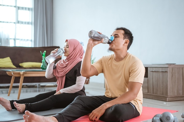 Asian fitness couple, man and woman exercising together at home drinking water from the bottle