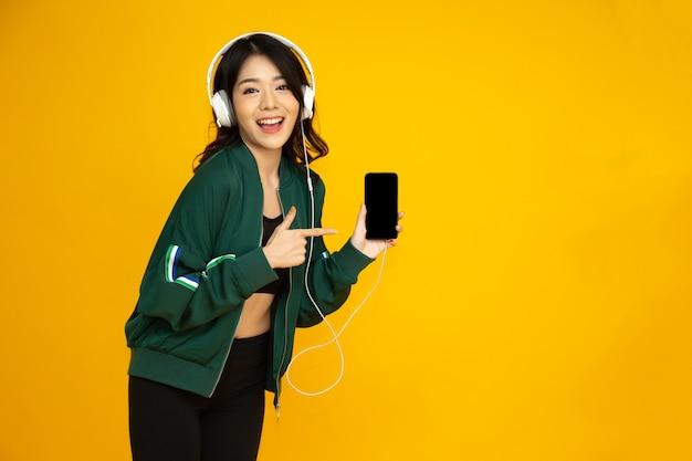 스마트폰으로 헤드폰을 끼고 음악을 듣고 노란색 배경에 격리된 전화를 가리키는 아시아 여성