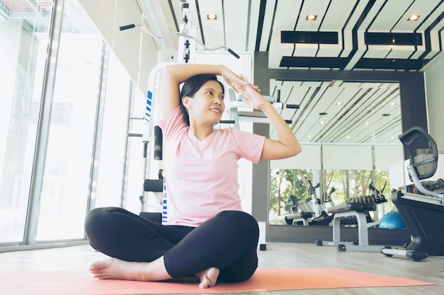 Asian fitness woman warm up before do exercise in gym, middle age female working out yoga