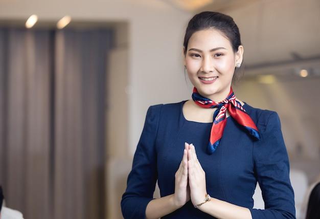 背景の航空機の助手席内の通路の真ん中で笑顔でポーズをとるアジアの客室乗務員