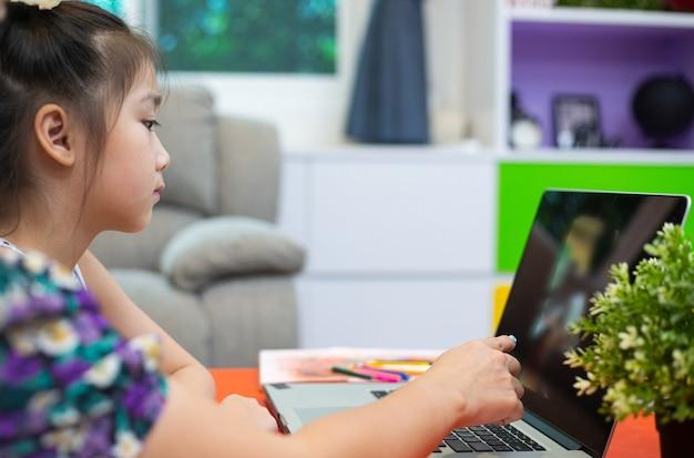リビングルームで一緒にオンラインで勉強するためにコンピューターを使用しているアジアの父と娘