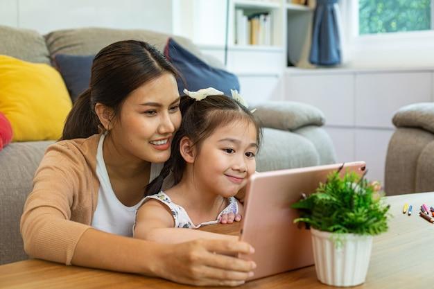 Азиатская мать и ее дочь используют планшеты для онлайн-обучения вместе