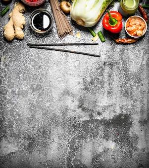 アジア料理。素朴な背景でアジア料理を調理するためのさまざまな食材。