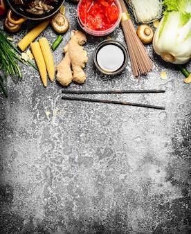 アジア料理。素朴な背景で中華料理やタイ料理を調理するためのさまざまな食材。