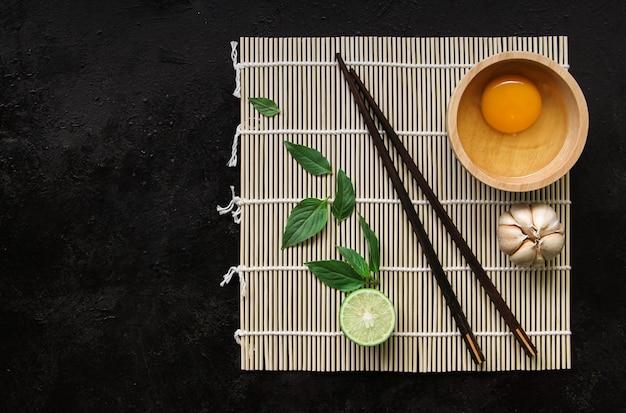 アジア料理の背景-灰色のコンクリートの背景にお茶と箸。