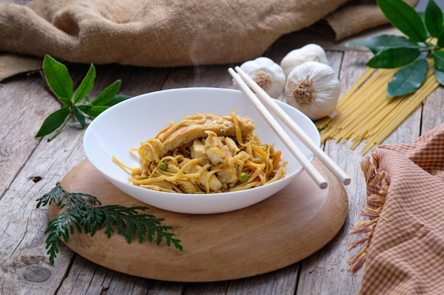 Asian food - bami goreng noodles on rustic table and chopsticks