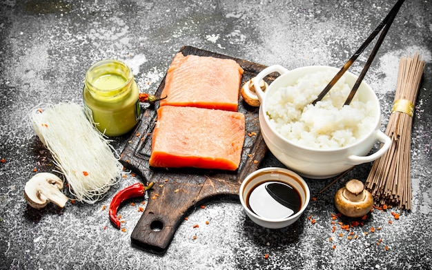 Asian food. boiled rice with a piece of salmon and a variety of ingredients. on rustic background . japanese table food.