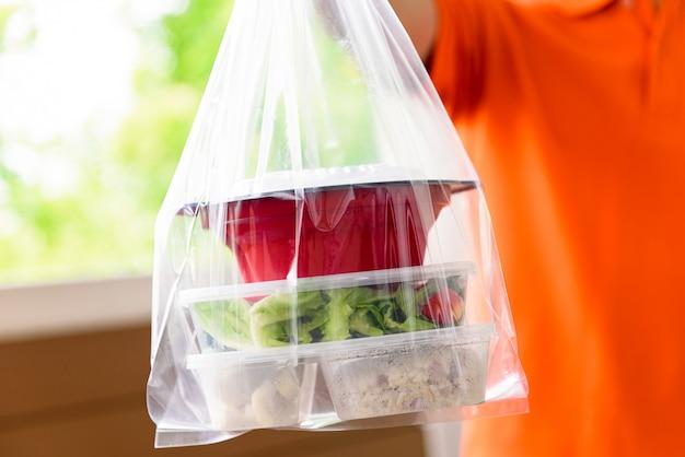 オレンジ色の制服を着た配達員が自宅で顧客に宅配したビニール袋に入ったアジアンフードボックス