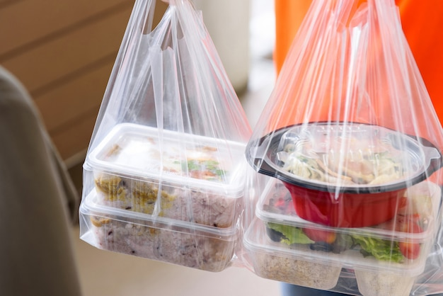 Asian food boxes in plastic bags delivered to customer at home by delivery man