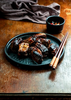 Asian food, caramelized pork ribs, dark   wooden background, chinese food