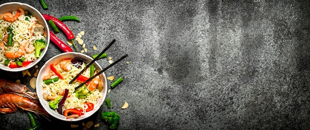 Азиатская еда. китайская лапша с овощами и креветками. на старом деревенском фоне.