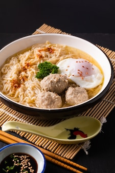 Asian food concept egg noodles ramen asian style with meatball on bamboo matt black background with copy space