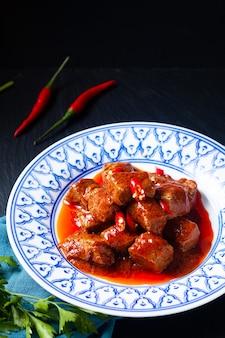 Концепция азиатской кухни sambal goreng daging говядина в красном карри, чили и паста из специй на черном фоне с копией пространства