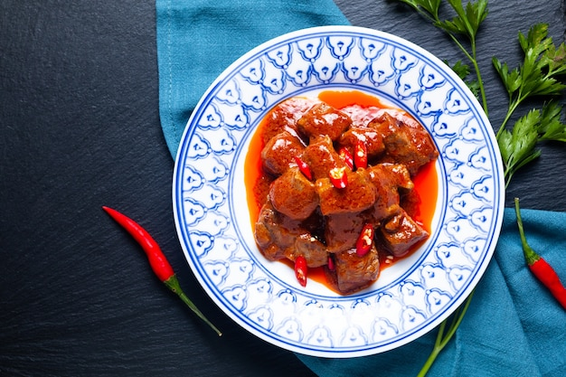 Asian food concept sambal goreng daging beef in red curry chili and spice paste on black background with copy space