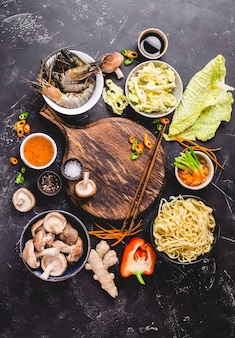 アジア料理のコンセプト。空の木板、麺類、野菜炒め物、エビ、ソース、箸。