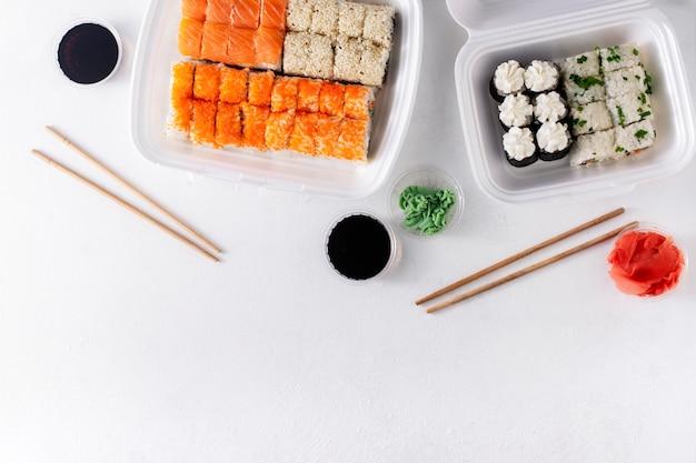 アジア料理の配達。二人で昼食。白い背景の上のトレイに日本の寿司。