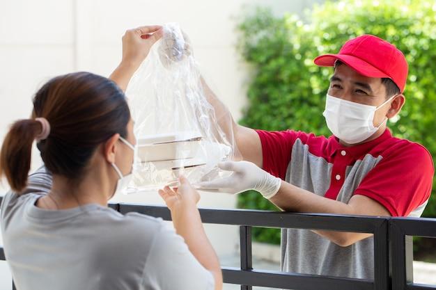 얼굴 마스크를 쓴 아시아 음식 배달원은 음식 상자와 함께 비닐 봉지를 들고 고객에게 배달합니다.