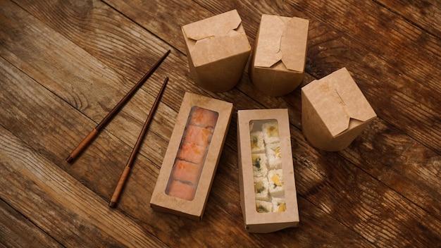 アジアの食品配達。寿司と中華鍋の包装。木製の背景に紙容器の食品