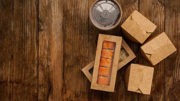 아시아 음식 배달. 초밥과 웍을위한 포장. 나무 테이블에 종이 용기에 음식